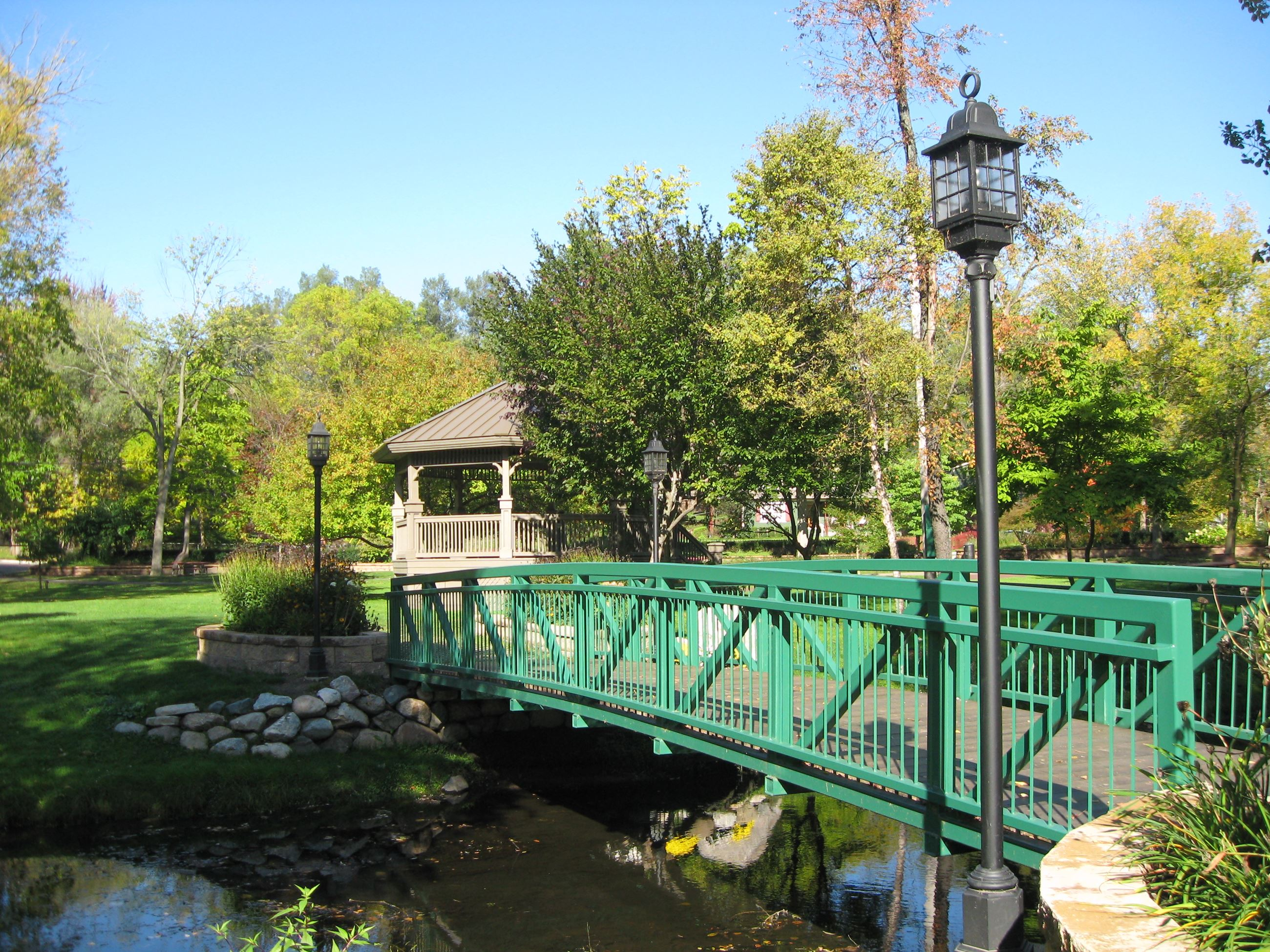 A bridge leading over a stream to a gazebo.